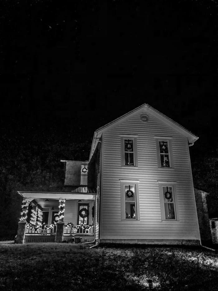 spotlight on farmhouse with Christmas lights