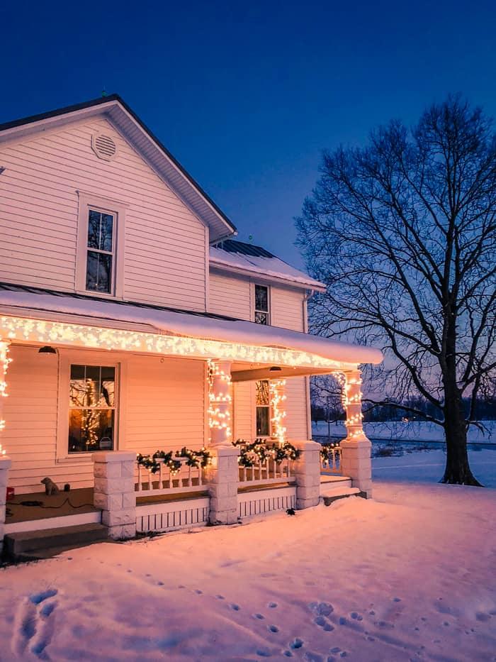 Christmas lights on farmhouse in snow