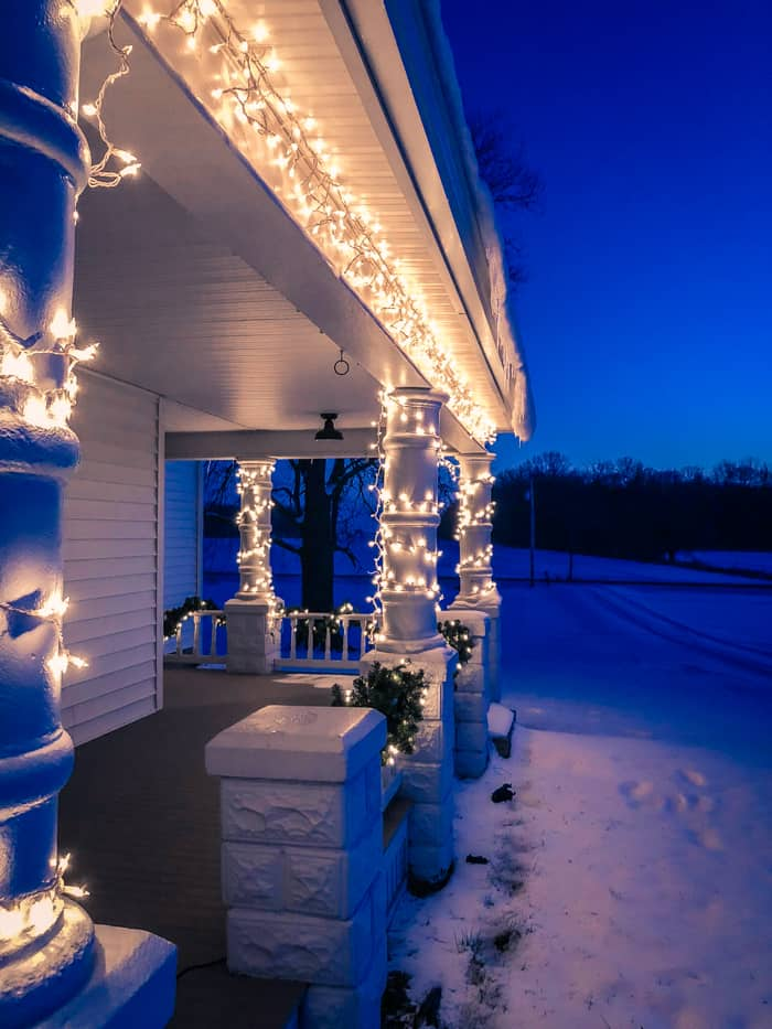 Christmas lights on farmhouse porch with snow