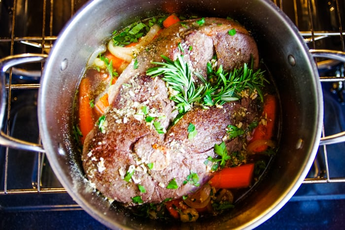 venison roast recipe in stock pot covered with rosemary and seasonings