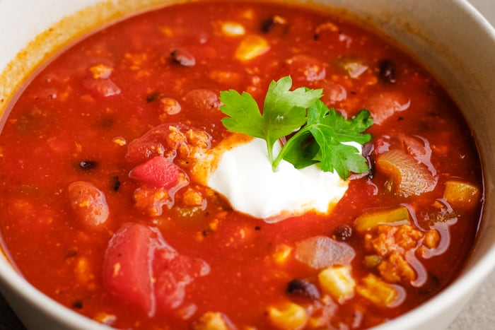 bowl of ground turkey chili with sour cream