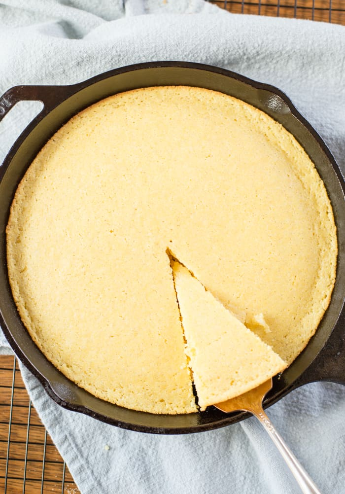 homemade cornbread in cast iron pan with slice