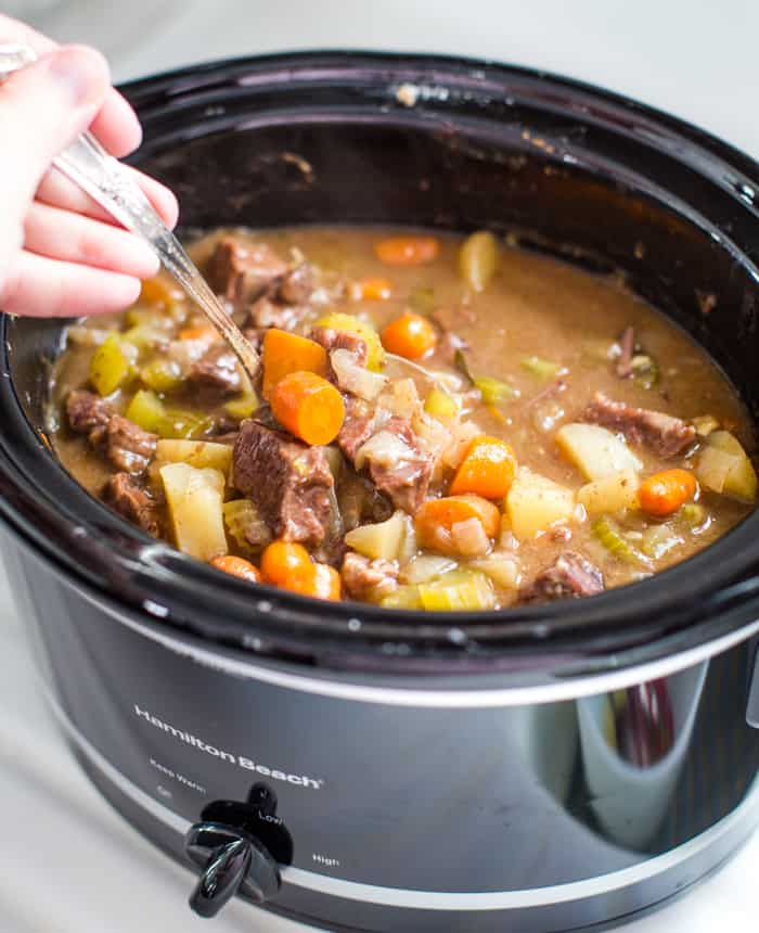old fashioned beef stew in slow cooker with spoon ladel