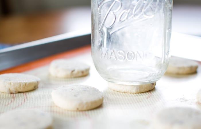 flatten cookies with glass on baking sheet