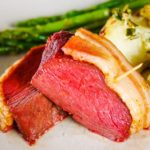 venison backstrap with bacon on plate with potatoes and asparagus