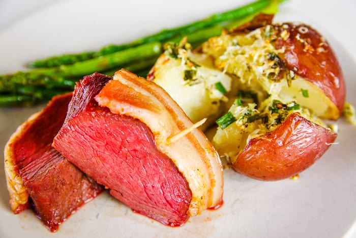 plate of smoked vension with potatoes and asparagus