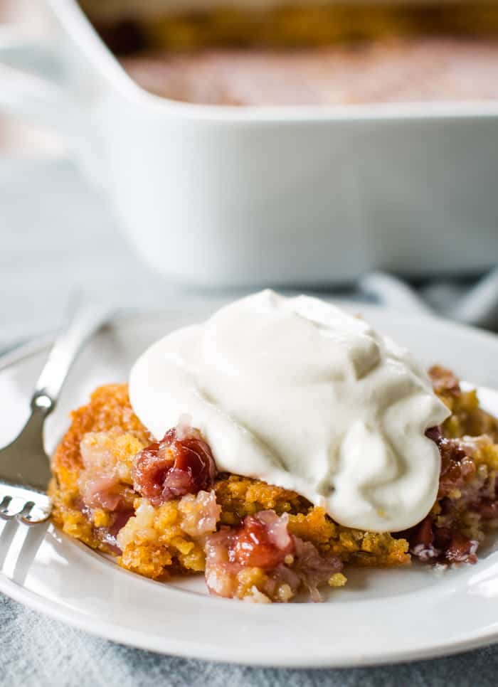 cherry pineapple dump cake with whipped cream on plate