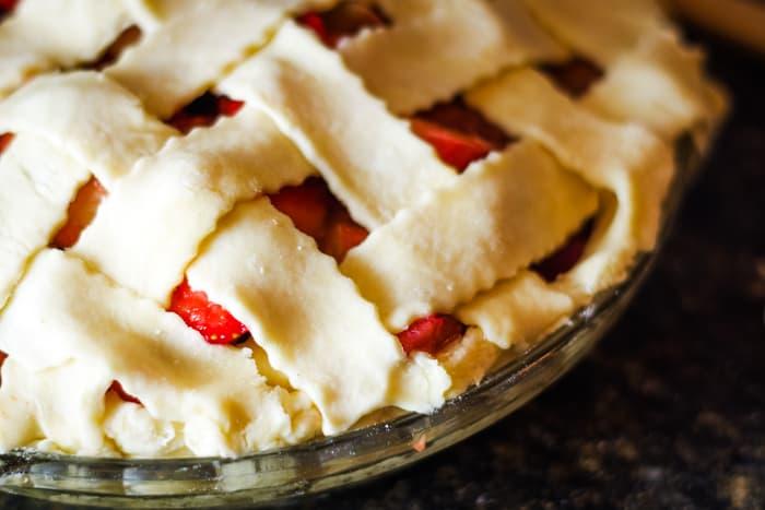 tucked in edges of lattice pie dough for strawberry rhubarb pie