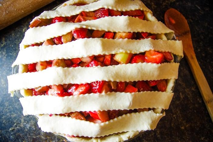 lattice pie dough over strawberry and rhubarb in pie crust