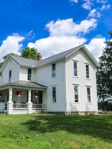 white farmhouse on hill