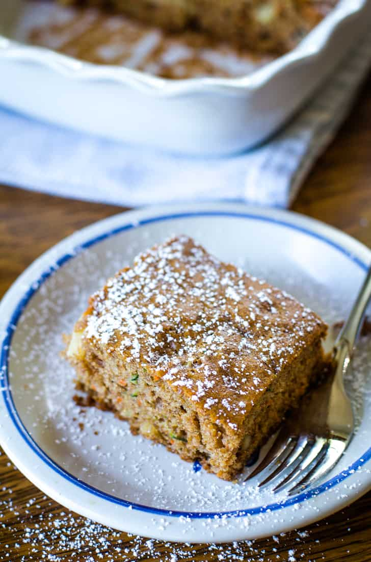sprinkled powdered sugar on zucchini cake on plate