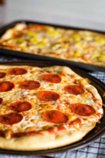 easy pizza dough recipe with pizzas on pan