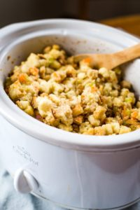 slow cooker stuffing in crockpot with wooden spoon