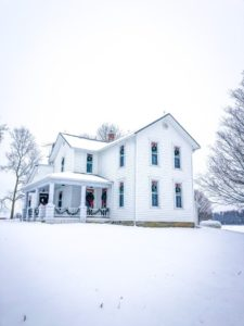 white farmhouse in snow with christmas decorations