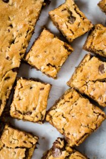 blonde brownie cut in squares on parchment paper