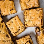 blonde brownie with nuts on parchment paper