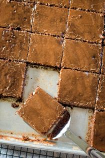 texas brownies in sheet pan with slice on spatula