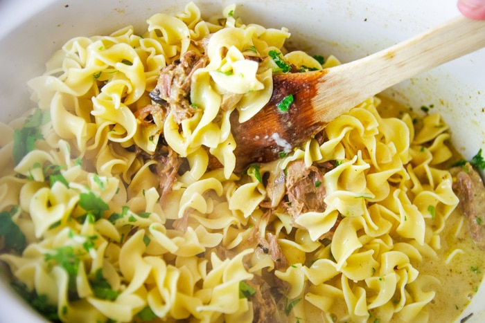 adding egg noodles to slow cooker with venison roast