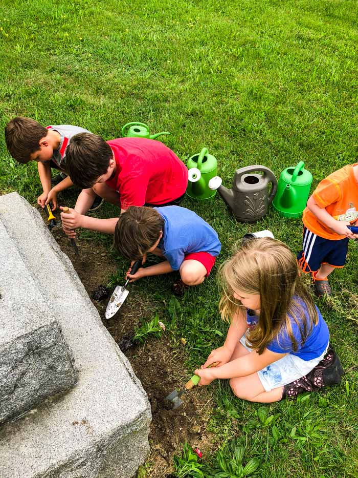 kids planting flowers at cemetary