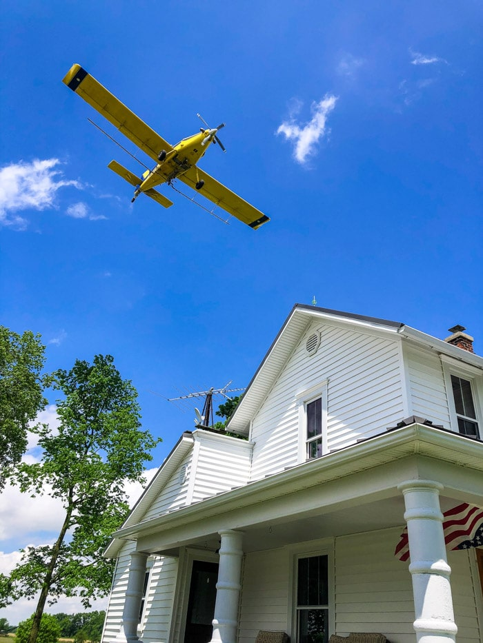 crop duster over house