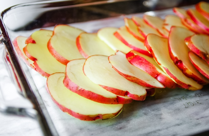 thinly sliced red potatoes in baking dish