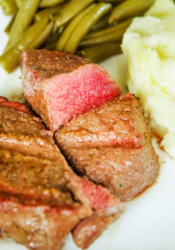 venison marinated steaks on plate