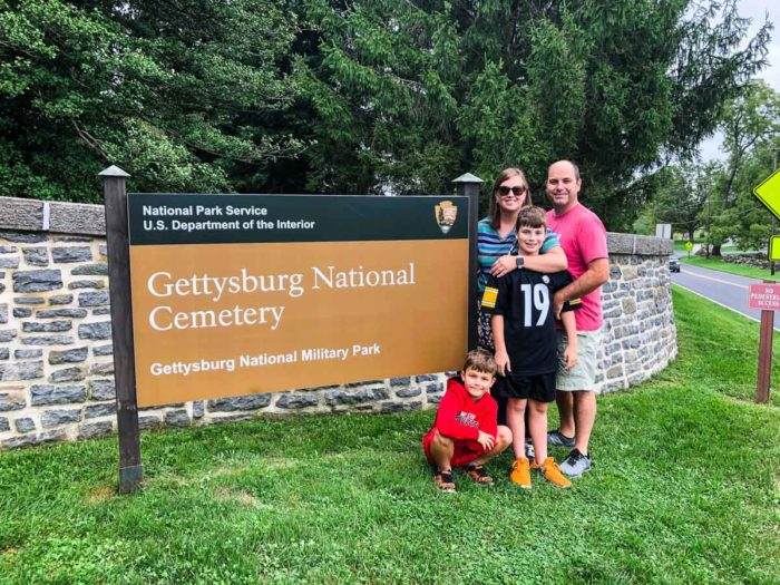 family in front of sign for Gettysburg National Cemetary