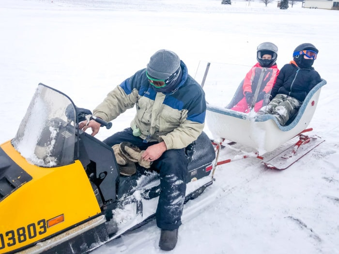 pulling sleigh on snow mobile