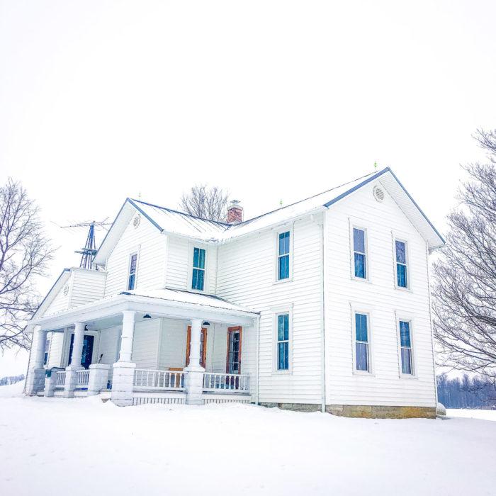 white farmhouse in snow