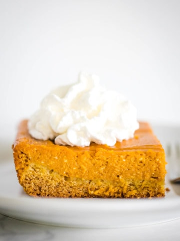 pumpkin gooey butter cake on plate topped with whipped cream