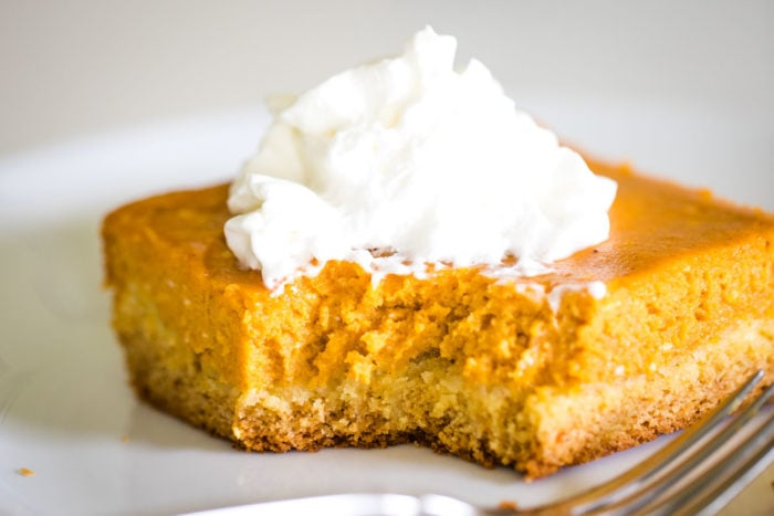 slice of pumpkin gooey butter cake on plate with whipped cream